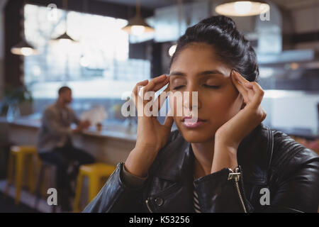 Young woman suffering from headache with friend in background at cafe - Stock Photo