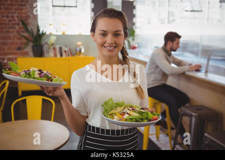 Portrait of waitress holding plates with salad while businessman using laptop at counter in cafe - Stock Photo