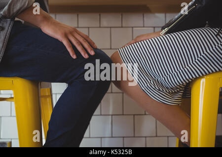 Mid section of young couple resting on stool at counter in cafe - Stock Photo