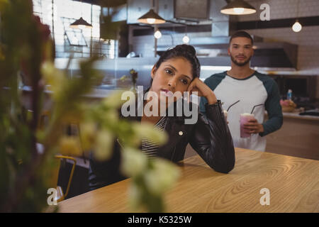 Bored young woman at table with male friend holding milkshake glasses in cafe - Stock Photo