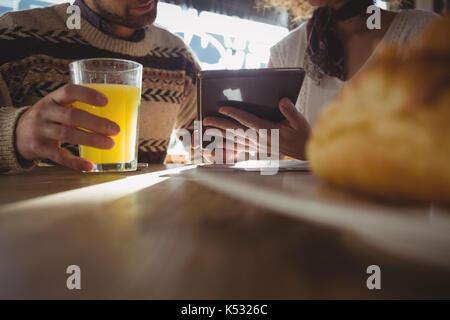 Mid section of woman with man using digital tablet at table in cafe