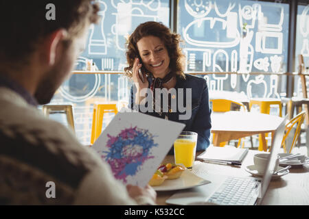 Man holding paper with painting by young woman talking on phone in cafe - Stock Photo