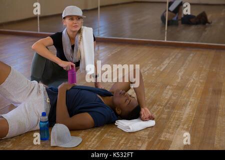 Tired male dancer sleeping by young woman on hardwood floor in studio - Stock Photo