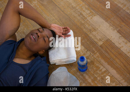 High angle view of male dancer sleeping on wooden floor in studio - Stock Photo
