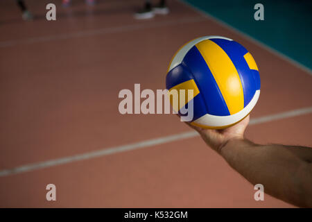 Cropped hand of sportsperson with volleyball at court - Stock Photo