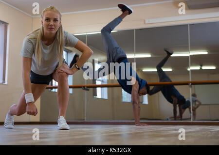 Young dancers practicing on wooden floor at studio - Stock Photo
