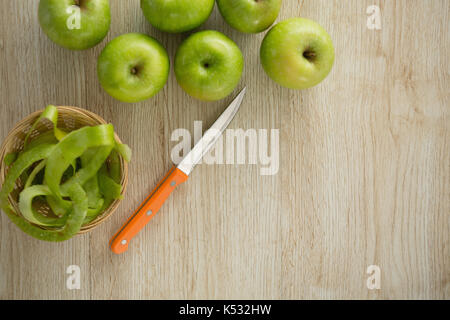 Overhead view of granny smith apples by peel in basket on table - Stock Photo