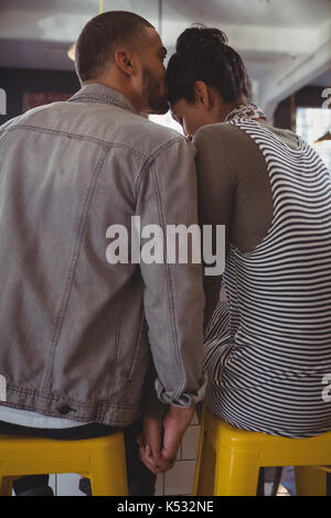 Rear view of man kissing on woman head at counter in cafe - Stock Photo