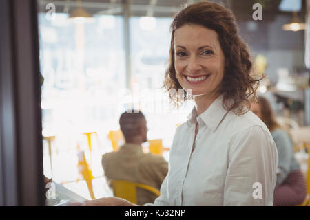 Portrait of happy businesswoman sitting in cafe - Stock Photo