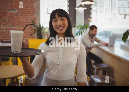 Portrait of waitress with smoothie glass while businessman using laptop at counter in cafe