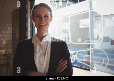 Portrait of confident female owner by window in cafe - Stock Photo