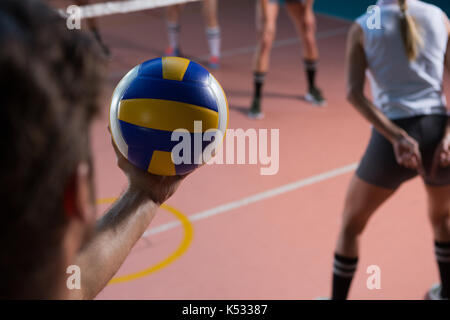 Cropped hand of player holding volleyball by female teammate at court - Stock Photo