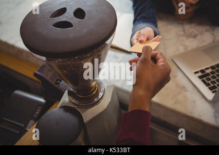 Cropped hand of male owner receiving payment from customer by grinder at counter in cafe - Stock Photo