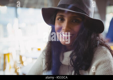 Portrait of smiling woman seen through glass in cafe - Stock Photo