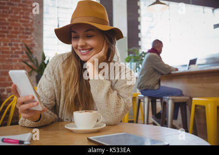 Smiling young woman with coffee using phone at table in cafe - Stock Photo