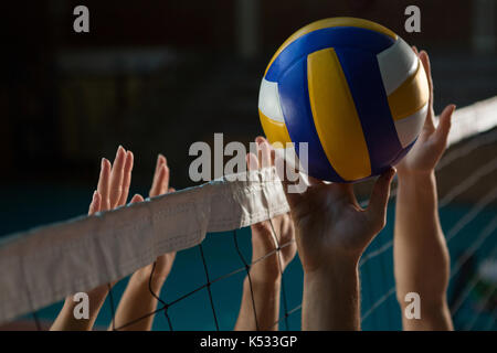 Cropped hands of players practicing volleyball at court - Stock Photo
