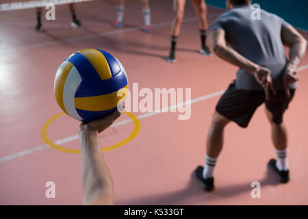 Cropped hand of player holding volleyball by teammate at court - Stock Photo