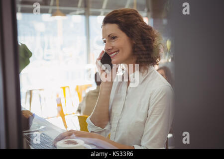 Young businesswoman using laptop while talking on mobile phone in cafe - Stock Photo