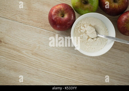 Directly above shot of flour in bowl by apples on wooden table - Stock Photo