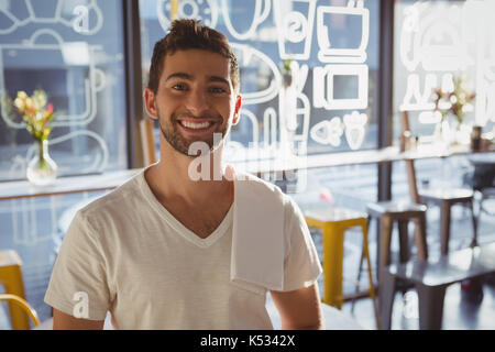 Portrait of happy young waiter in cafe on sunny day - Stock Photo