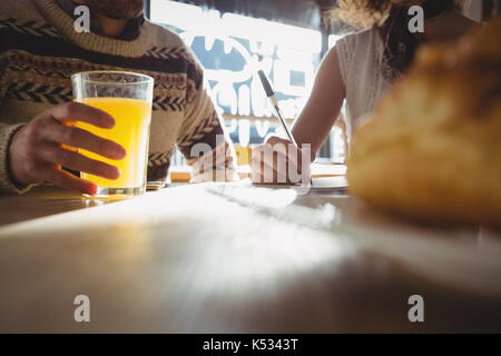 Midsection of young man with woman having juice at table in cafe - Stock Photo