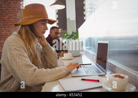 Young businesswoman using laptop at counter in cafe - Stock Photo