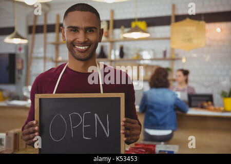 Portrait of smiling owner with open sign standing in cafe - Stock Photo