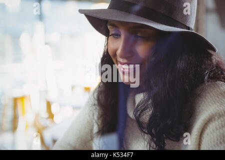 Close-up of young woman wearing hat in cafe - Stock Photo