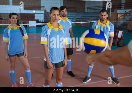 Cropped hand of female coach holding ball practicing with volleyball players at court - Stock Photo