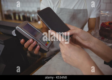 Cropped hand of customer making contactless payment with waiter holding credit card reader in cafe - Stock Photo