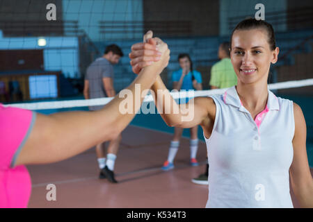 Cropped image of volleyball player holding hand with female teammate at court - Stock Photo