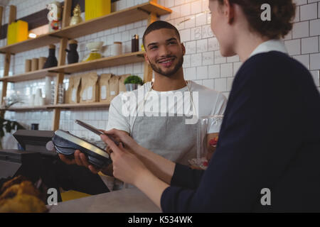 Young waiter showing credit card reader to female owner in cafe - Stock Photo