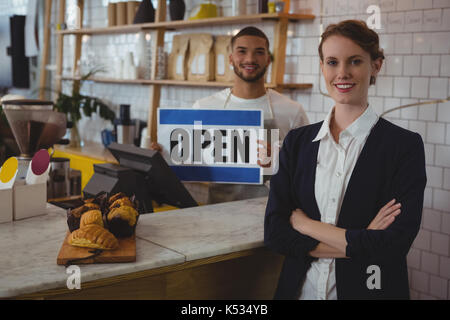 Portrait of confident female owner with waiter holding open sign at counter in cafe - Stock Photo