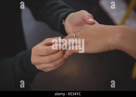 Cropped image of man putting ring on woman finger at cafe - Stock Photo