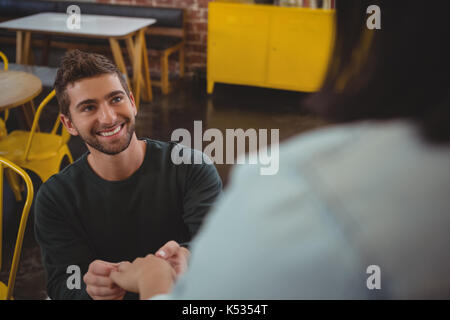 Smiling young man holding girlfriend hand at cafe - Stock Photo
