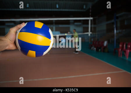 Cropped hand of sportsperson holding volleyball at court - Stock Photo