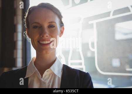 Portrait of happy female owner by window in cafe - Stock Photo