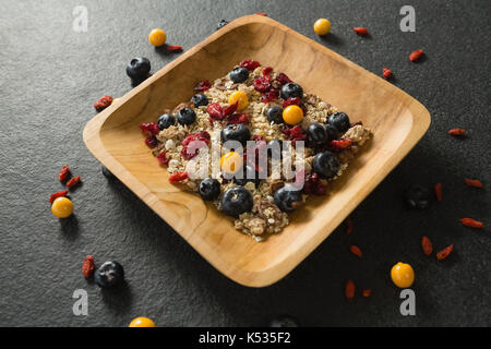 Close-up of breakfast cereal with fruits on black background - Stock Photo