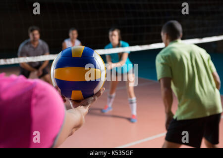 Cropped hand of female player with teammates holding volleyball at court - Stock Photo