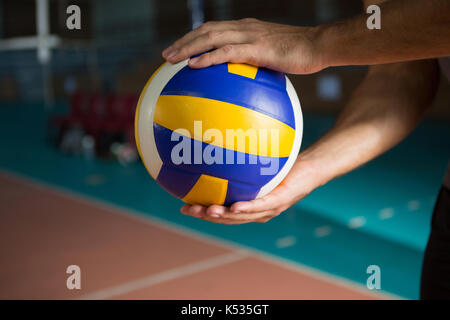 Cropped hands of player holding volleyball at court - Stock Photo