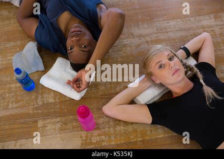 Portrait of tired dancers relaxing on hardwood floor in studio - Stock Photo