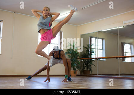 Full length of female dancer with young friend jumping in studio - Stock Photo