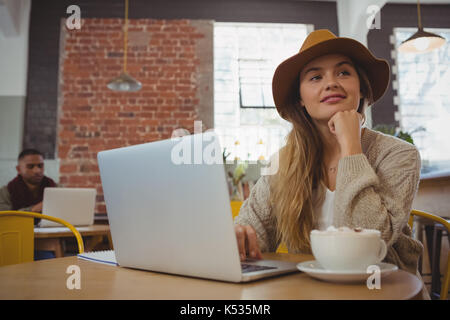 Thoughtful young woman with laptop looking away in cafe - Stock Photo