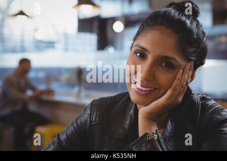 Close-up portrait of smiling woman with friend in background at cafe - Stock Photo