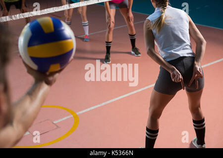 Cropped hand of player holding volleyball with female teammate gesturing at court - Stock Photo