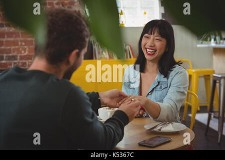 Man putting ring on happy young woman finger at cafe - Stock Photo