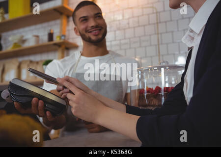 Waiter showing credit card reader to female owner at counter in cafe - Stock Photo