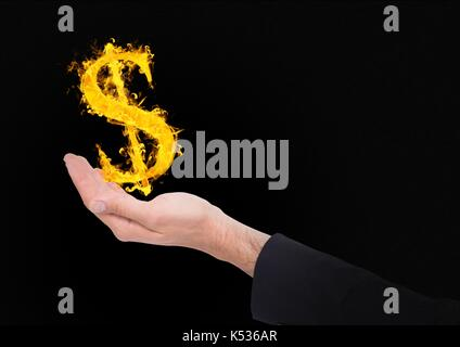 Digital composite of hand with dolar  fire icon over. Black background - Stock Photo