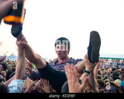 A young man crowd surfs over the audience at the Victorious music festival in Portsmouth, England - Stock Photo