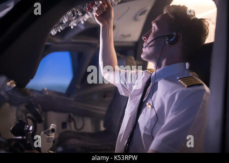 Young male pilot switching control in airplane cockpit seen from window - Stock Photo